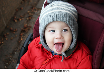 Cute naughty baby boy shows tongue and tease. Boy in winter...