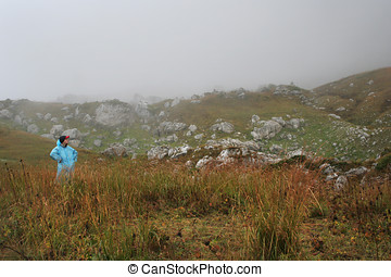 Man traveler in mountain fog looking forward and ready for adventures