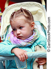 Dissatisfied little girl in a pushchair