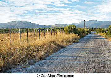 Old Asphalt Road With Mountain Background. Old Fashioned Wooden Fence With a Rural Landscape in the Background.