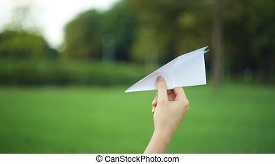 woman holding a paper airplane in the park