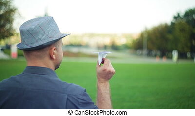 man holding paper aircraft in stretched hand before...