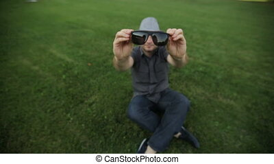 man in the hat wears sunglasses sitting on the grass