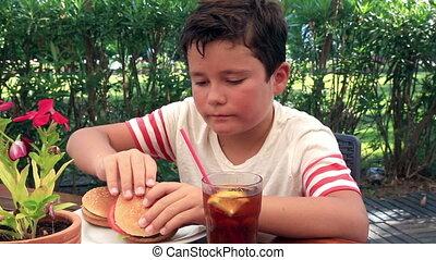 Hungry young boy eating hamburger at the cafe