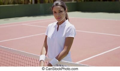 Smiling Young Woman Holding Racket on Tennis Court