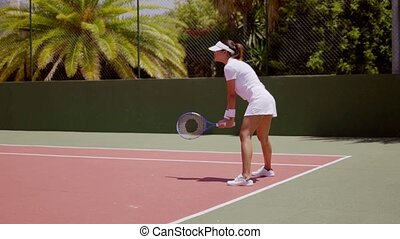 Attractive tennis player standing ready to receive -...