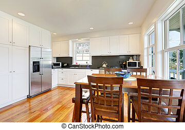 Design of kitchen room interior with white cabinets and black counter tops