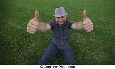 fashion young man wearing hat is sitting on grass and posing