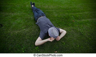 man with a hat lying on the grass in the park