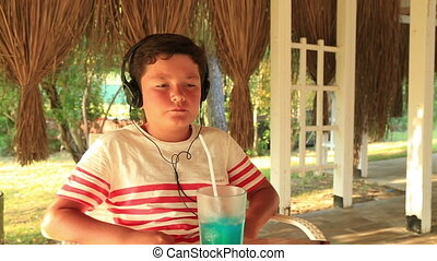 Little boy listening to music at the cafe