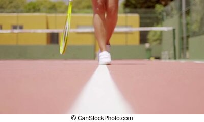 Woman walking along a line on a tennis court - Low angle...