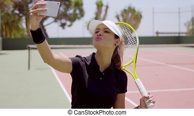 Attractive tennis player taking a selfie on her mobile phone...