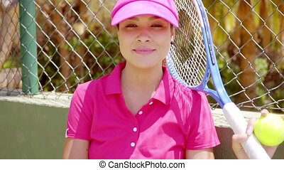 Relaxed confident young woman tennis player