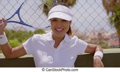 Smiling woman leaning on fence with tennis racket