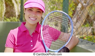 Excited young female tennis player giving a V-sign - Excited...
