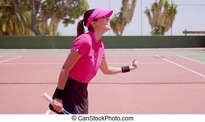 Excited young woman tennis player cheering