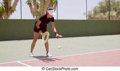Athletic woman tennis player serving the ball tossing it in...