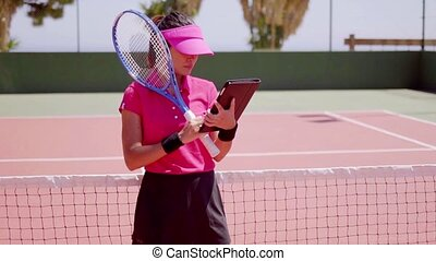 Woman checking schedule for tennis game - Serious attractive...
