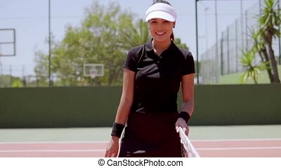 Pretty athlete wearing black outfit and visor while standing...