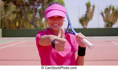 Gorgeous young tennis player giving a thumbs up - Happy...