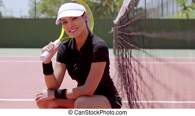 Attractive athlete crouched next to net while holding racket...