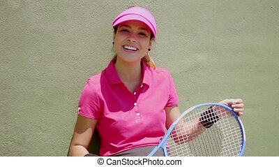 Laughing tennis player holding racket on her knees while...