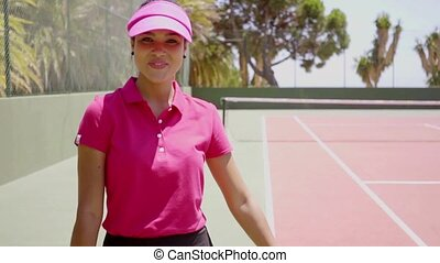 Pretty young woman tennis player turning to look back at the...