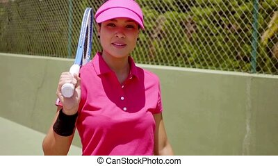 Attractive smiling tennis player holding racket against her...