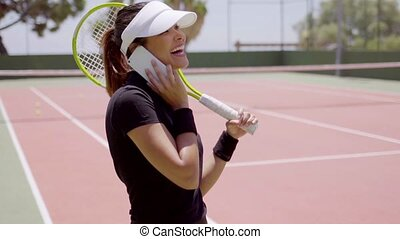 Tennis player on phone at court outside - Single female...