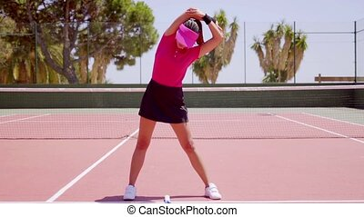 Young woman warming up before a game of tennis standing on...