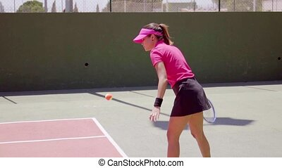 Novice tennis player doing an underhand serve - Novice...