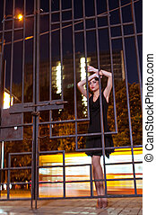 Pretty woman posing in cage outdoors at night - Emotions...