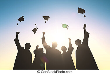silhouettes of students throwing mortarboards - education,...