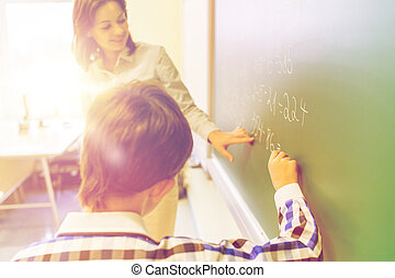 school boy with teacher writing on chalk board - education,...