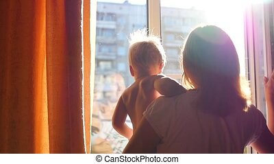 a girl with a child looking in through the window