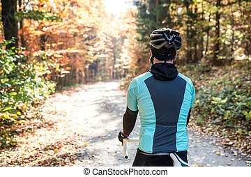 Young sportsman riding his bicycle outside in sunny autumn...