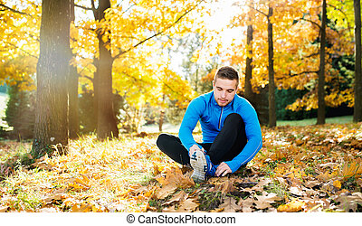 Runner sitting on the ground, tying shoelaces, autumn nature...