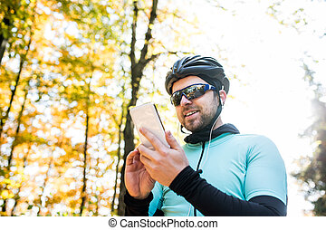 Young sportsman riding bicycle, holding smartphone, sunny...