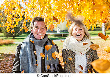 Active senior couple in autumn park throwing leaves - Active...