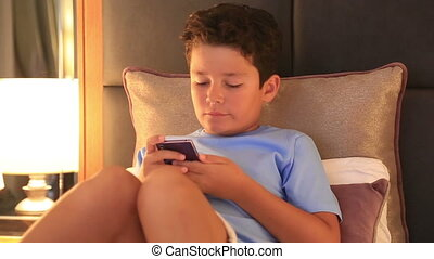 little boy with smartphone lying on a bed - Child using...