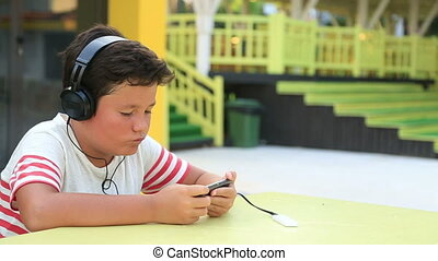 Little boy with headphone using smartphone - Young boy...
