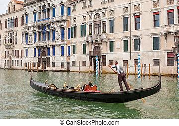 Venetian gondolier on gondola - Venetian gondolier punting...