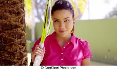 Woman with tennis racket beside palm tree - Calm beautiful...