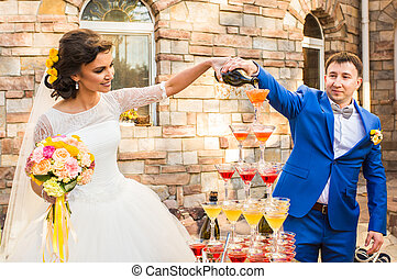Wedding couple is pouring champagne outdoors. Colorful...
