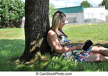 Girl reading book under tree in shade - Young white...