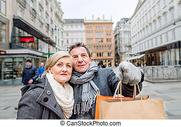 Senior couple shopping in centre of the city. Winter -...