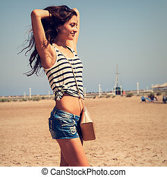 Beautiful fit enjoying woman posing on the beach in blue...