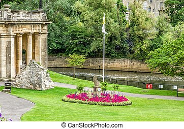 Green park and buildings along River Avon, Bath, England -...