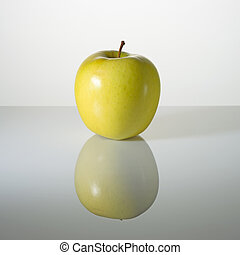 Green apple on a surface with reflection