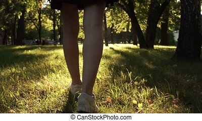 Young female legs walking in a park
